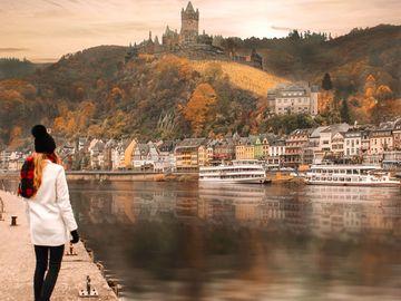 Ansicht auf eine Frau am Moselufer Cochem mit Blick auf die Reichsburg.