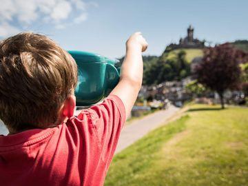 Blick über die Schulter eines Jungen mit Fernglas auf die Reichsburg Cochem.