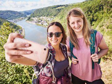 Ansicht auf zwei Frauen bei einem Selfie mit der Mosel im Hintergrund.